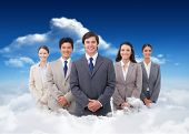 Smiling salesteam standing against bright blue sky with clouds
