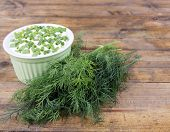 Plastic round bowl of cream with a tuft of dill near it on wooden background
