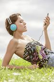 Young woman listening to music through MP3 player using headphones while lying on grass against sky