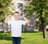 advertising, gesture, people and childhood concept - smiling little boy in white blank t-shirt with