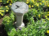 pic of sundial  - Traditional garden sundial shows the time by the shadow cast by the sun - JPG