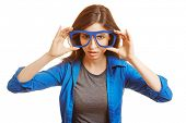 Young woman holding fake nerd glasses in front of her face