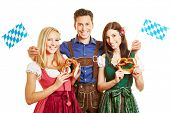 Happy man and two smiling women in traditional bavarian outfit with dirndl and leather pants