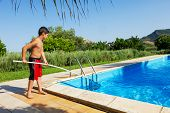 young boy retrieves objects from the pool in exterior