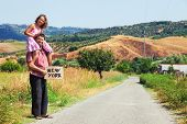 father and daughter hitchhiking along a road