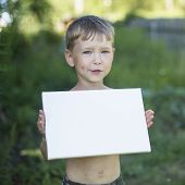 Little boy holding clean white sheet paper, outdoors (banner for your message)