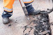Road Worker Breaking Street Asphalt With Jackhammer