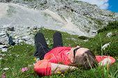 Young Woman Relaxing In A Mountain Meadow