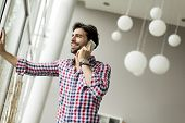stock photo of people talking phone  - Young businessman talking on the phone in the modern office - JPG