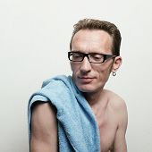 Handsome naked man in spectacles with a blue towel on his shoulder after bath smiling