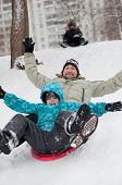 Dad And Son Riding A Frozen Hill