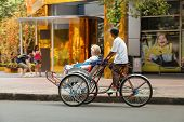 A man is driving a foreigner by pedicab on the center of Saigon