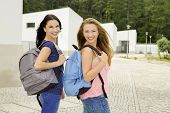 Two beautiful teenage students walking while looking back and smiling