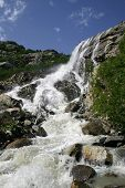 Alpine Waterfall In Mountain