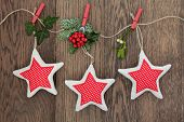 Christmas star decorations with holly, ivy, fir and mistletoe hanging on a string line over oak back