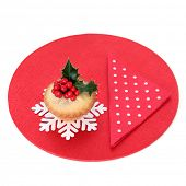Christmas mince pie cake with holly and red polka dot serviette on a cake mat over white background.