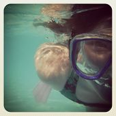 fun instagram image of young girl underwater snorkelling