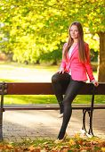 Fall. Full Length Girl Woman Sitting On Bench In Autumnal Park Forest