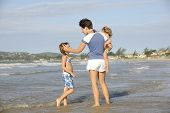 Happy mother and daughters having fun on the beach.