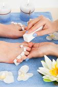 Pedicurist Filing Toenails Of Woman