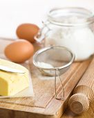 foto of flour sifter  - Baking ingredients with flour eggs and butter on rustic board selective focus on butter knife