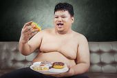 Cheerful Fat Man Eating Donuts