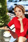 Beautiful young woman with mobile phone sitting in cafe