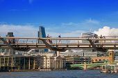 LONDON, UK - AUGUST 9, 2014: Millennium bridge next to St. Paul cathedral and Tate gallery with peop