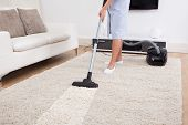 stock photo of housekeeper  - Cropped image of young maid cleaning carpet with vacuum cleaner at home - JPG