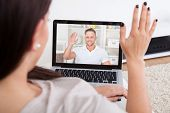 pic of video chat  - Cropped image of young woman using laptop for video conference at home - JPG