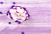 beautiful artificial eustoma on purple wooden background