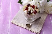 Healthy breakfast - yogurt with  fresh grape and apple slices and muesli served in glass bowl, on co
