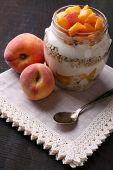 Healthy breakfast - yogurt with  fresh peach and muesli served in glass jar, on wooden background