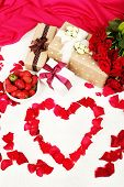 Romantic still life with strawberry, gift boxes and petals of roses on bed