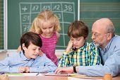 Young Schoolchildren In Class With Their Teacher