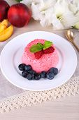 Round shaped cake with berries on plate on lace napkin on wooden background