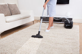 picture of maids  - Cropped image of young maid cleaning carpet with vacuum cleaner at home - JPG
