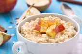 image of cinnamon  - Tasty oatmeal with apples and cinnamon in a bowl - JPG