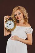 Pregnant woman with an alarm clock on a dark background.