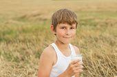 Teenage boy holding glass of raw fresh milk