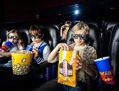 stock photo of watching movie  - Siblings having snacks while watching movie in 3D cinema theater - JPG