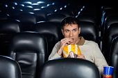 Mid adult man eating popcorn while watching movie in cinema theater