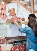 Mature man selling fresh packed of sausages to female customer in butchery