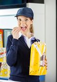 Portrait of young female worker eating popcorn from paperbag at cinema concession stand
