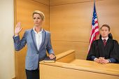 stock photo of court room  - Witness taking an oath in the court room - JPG