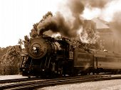 Steam engine leaving station in sepia tone