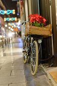 Retro bike with fairy lights and a poinsettia on the basket in a Christmas decorated street