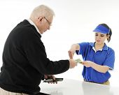 A teen fast-food server returning change to a senior man customer.  On a white background.