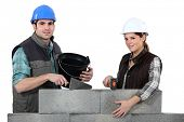 stock photo of pecker  - Couple constructing wall - JPG