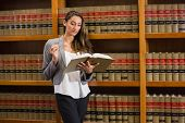 image of laws-of-attraction  - Pretty lawyer reading in the law library at the university - JPG